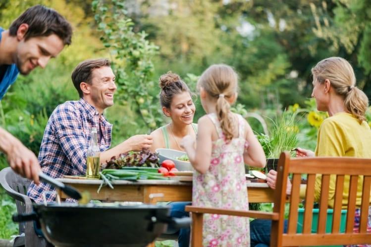 Famille autour d'un barbecue dans le jardin