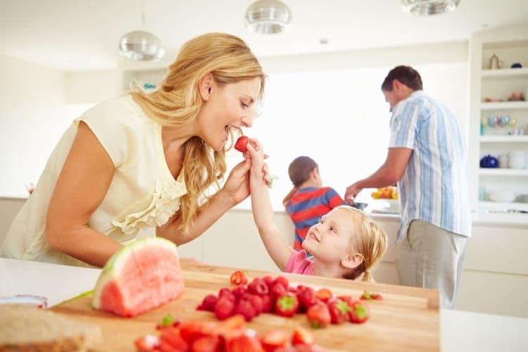 Mère et enfant grignotant des fraises fraîches
