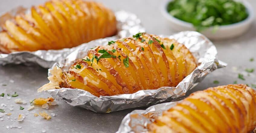 Pommes de terre Hasselback dans des papillotes en aluminium avec du fromage et des fines herbes