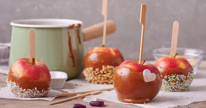 Pommes d'amour au caramel décorées d'éclats de noisettes sur du papier cuisson