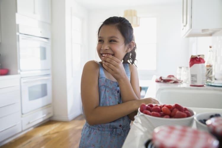 un enfant heureux grignote des framboises fraîches